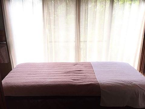 サロン風景 優しい光の差し込む部屋とベッド